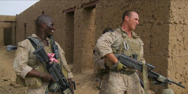 Cpl. Kionte Storey (left) and an unnamed Marine, deployed in the Middle East.