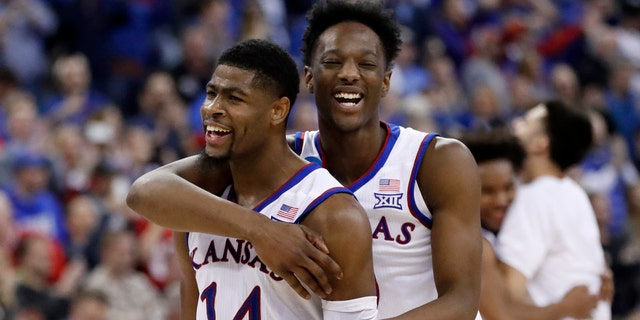 Kansas' Malik Newman (14) and Marcus Garrett celebrate after defeating Duke 85-81 in overtime a regional final game in the NCAA men's college basketball tournament Sunday, March 25, 2018, in Omaha, Neb. (AP Photo/Nati Harnik)