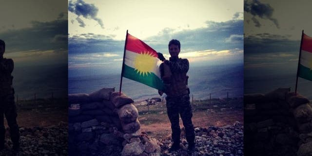 Kurdish Peshmerga soldier waves the Kurdish flag while manning a front line in the battle against ISIS