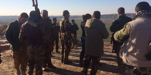 Kurdish forces stand near Kirkuk, staring off at the ISIS front on the horizon.