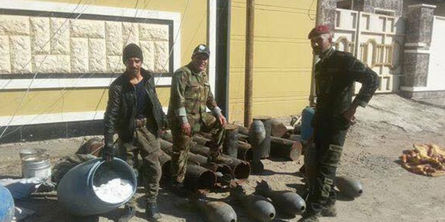 Kurdish fighters stand with seized - and unmaintained - ISIS armaments.