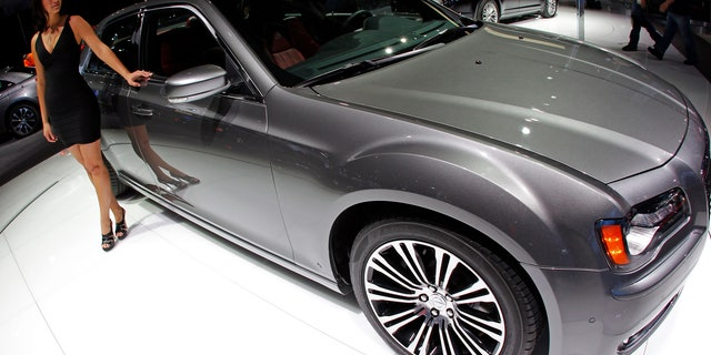 April 21, 2011: A model stands by a Chrysler 300 S on display at the New York International Auto Show in New York City