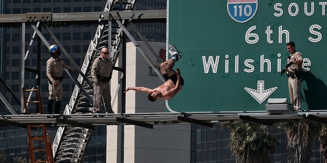 Alexander Dunn does a backflip off a sign over the 110 Freeway in Los Angeles onto a landing pad below on June 27, 2017.