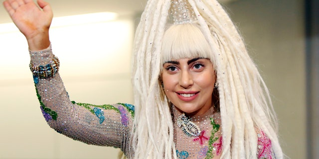 August 12, 2014. Singer Lady Gaga waves upon her arrival at Narita international airport, east of Tokyo.