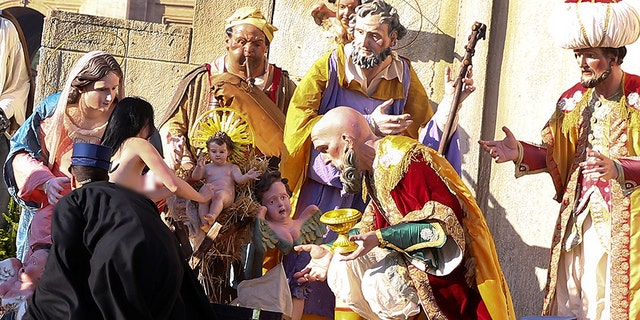Vatican gendarmes attempt to block a topless activist of women's rights group Femen, who tries to reach the Nativity scene in Saint Peter's square in the Vatican.