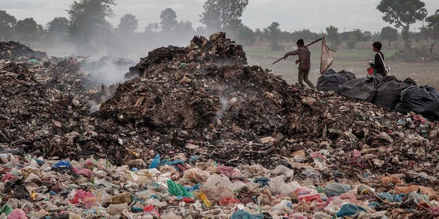 SIEM REAP, CAMBODIA - JUNE 11:  A couple of young boys walk between tons of rubbish where they work daily in the Anlong Pi landfill on June 11, 2014 in Siem Reap, Cambodia. Dozens of children work every day in the Anlong Pi landfill, which is situated only few kilometres aways from the world famous Angkor temples, visited by more than 3 million tourists every year. Despite the Cambodian government's commitments and legal responsibilities to end child labor - enshrined in its ratification of relevant international covenants, domestic laws and the implementation of several national policies aimed at ending child labor - it remains a significant concern in Cambodia, where almost a third of the population lives on less than a dollar per day. Child labor is a consequence of this poverty, often resulting from a family's inability to support itself. According to a recent report from the International Labour Organisation (ILO), an estimated 19.1% of the close to 4 million children in Cambodia between the ages of 5 and 17 engage in economic activities. An estimated 56.9% of those children are child labourers, with a third of them being involved in hazardous activities mostly in the agriculture, forestry and fishing sectors. (Photo by Omar Havana/Getty Images)