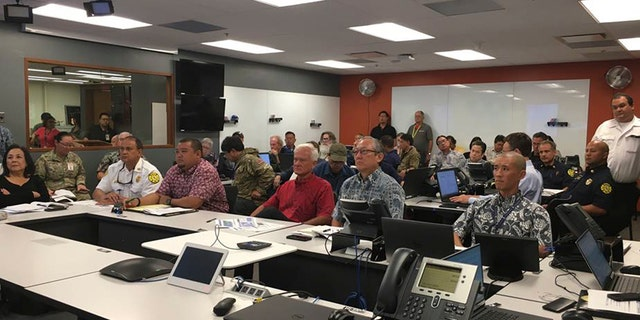 In this photo provided City and County of Honolulu, Mayor Kirk Caldwell, center, receives a briefing from the Central Pacific Hurricane Center on Hurricane Lane at the Emergency Operations Center in Honolulu, Tuesday, Aug. 21, 2018.