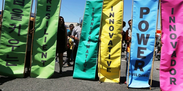 Inspirational messages in multiple languages are seen on banners at the corner of Florence and Normandie, the flash point of riots that erupted after the 1992 acquittal of four white police officers in the beating of black motorist Rodney King, on the 25th anniversary, in Los Angeles, Saturday, April 29, 2017.