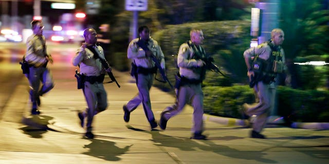 Police run to cover at the scene of a shooting near the Mandalay Bay resort and casino on the Las Vegas Strip, Sunday, Oct. 1, 2017, in Las Vegas. Multiple victims were being transported to hospitals after a shooting late Sunday at a music festival on the Las Vegas Strip.