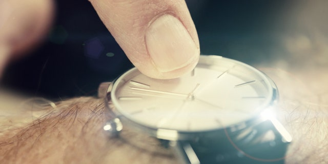 A man's finger taps impatiently on the dial of a watch, indicating time pressure or lateness.