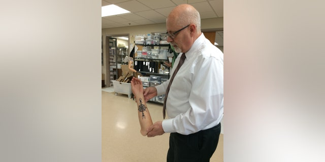 Dave Laufer, director of orthotics and prosthetics at Walter Reed National Military Center, displays a customized limb featuring a tattoo.