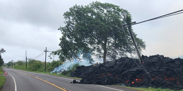 A fast-moving lava flow covers Highway 132 in Hawaii on Tuesday, taking out utility poles and knocking out power in the area.