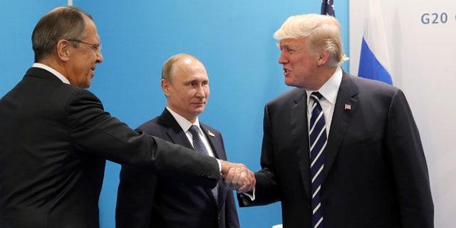 U.S. President Donald Trump, right, greets Russian Foreign Minister Sergey Lavrov, left, prior his talks with Russian President Vladimir Putin, center, during the G20 summit in Hamburg Germany, Friday July 7, 2017. (Mikhail Klimentyev, Kremlin Pool Photo via AP)