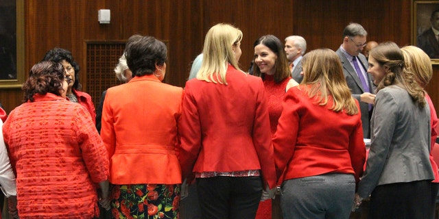 Female members of the Arizona House, from Republican and Democratic parties, hold hands to express support for Rep. Michelle Ugenti-Rita, middle facing camera, as the House prepares to vote to possibly expel a member for sexual harassment in Phoenix, Ariz., Thursday, Feb. 1, 2018. An investigation of Republican Rep. Don Shooter was prompted in an October complaint by Ugenti-Rita, also a Republican. (AP Photo/Bob Christie)