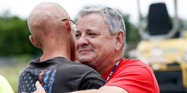 Tony Heineman, advancement and development officer for Soldier's Wish, hugs Cody Nichols, left, after presenting him with new lawn equipment at Bloss Equipment in Tulsa, Okla., on Friday, June 22, 2018.