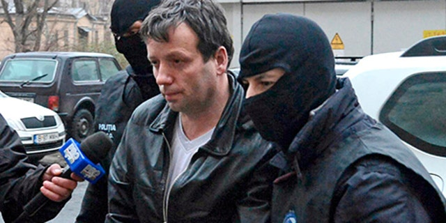 Marcel Lehel Lazar, 40, is escorted by masked policemen in Bucharest, after being arrested in Arad, 550 km (337 miles) west of Bucharest January 22, 2014.