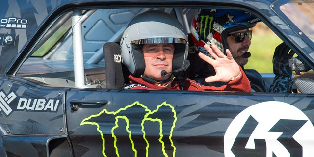 Actor and Top Gear presenter  Matt LeBlanc, left, waves , as he sits with  rally driver Ken Block during filming of BBC Top Gear in Westminster, London on Sunday Sunday March 13, 2016 .