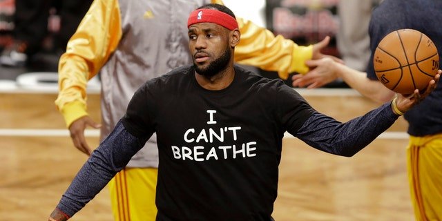 "Cleveland Cavaliers' LeBron James wears a T-shirt reading ""I Can't Breathe,"" protesting the death of Eric Garner while being arrested by NYPD officers, warms up before an NBA basketball game against the Brooklyn Nets in New York."
