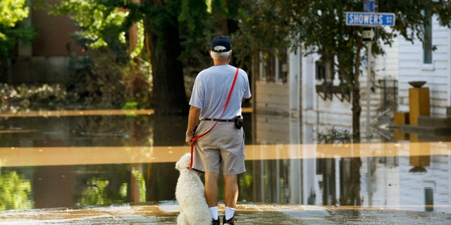 Sept. 10: John Wimer, and his dog Carlie, look at his neighborhood in the Shipoke area after flooding caused by the remnants of Tropical Storm Lee in Harrisburg, Pa.