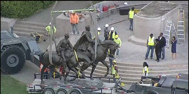 A statue of Robert E. Lee is removed from its pedestal in the Oak Lawn section of Dallas Thursday night.