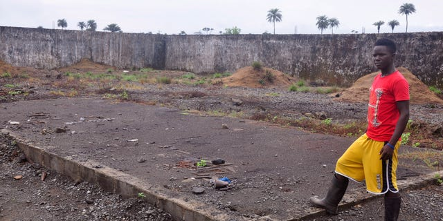 In this photo taken Saturday, March 26, 2015, a boy, stands next to a place that was used to stack bodys of Ebola victims at a crematorium in Boys Town on the outskirts of Monrovia, Liberia.