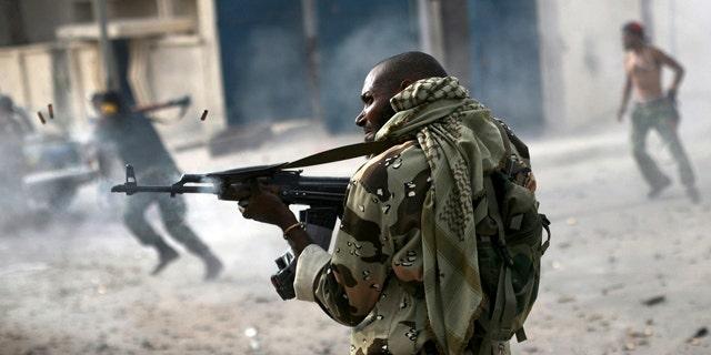Oct. 19, 2011: A Libyan rebel fighter fires his machine gun toward loyalist positions down town Sirte, Libya.