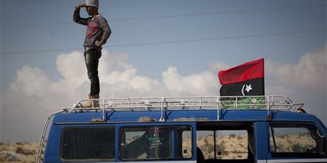 A Libyan man stands on top of his car looking at the frontline of fighting between rebels and Muammar al-Qaddafi's forces outside the city of Ajdabiya in eastern Libya March 22.