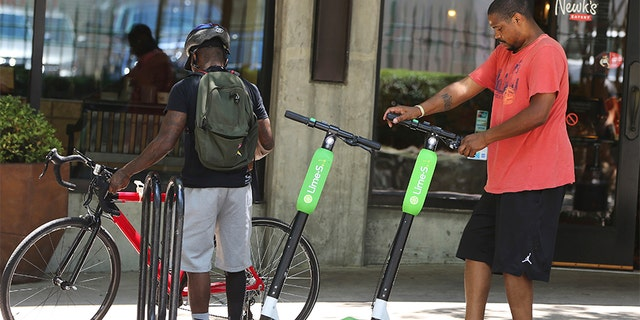 A man parks his rented dockless scooter outside of a restaurant in Atlanta. Lawsuits and cease-and-desist orders have quickly followed the arrival of California-based scooter companies.