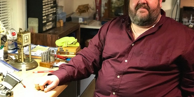 Lindsay Rasberry poses for a photo at his clock repair workshop located inside his home in Tupelo, Miss. Rasberry has trained ten people over the years and hopes more people practice horology.