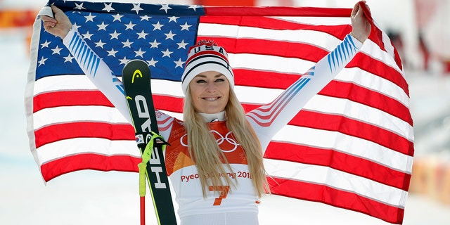 Bronze medal winner Lindsey Vonn celebrates during the flower ceremony for the women's downhill at the 2018 Winter Olympics.