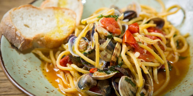 Homemade pasta with seafood and cherry tomatoes on wooden table