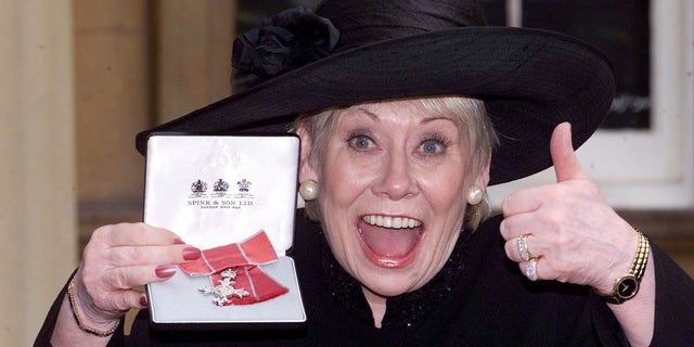 """FILE - This is a Oct. 24, 2000  file photo of British  actress Liz Dawn at Buckingham Palace, London after she received an MBE.  Liz Dawn, the actress who played tart-tongued Vera Duckworth in the long-running British soap opera """"Coronation Street,""""  died on Monday Sept. 25, 2017 . She was 77. (Sean Dempsey/PA via AP)"""
