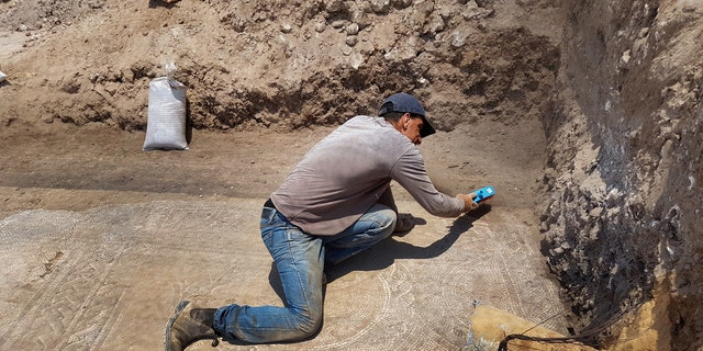 Uncovering the mosaic. (Photo: Amir Gorzalczany, Israel Antiquities Authority)