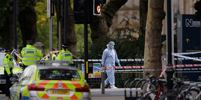 Britain's Police and a forensic investigator at the scene of an incident in central London, Saturday, Oct. 7, 2017.