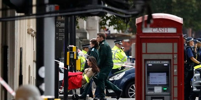 Ambulance personnel push a woman on a stretcher at the scene of an incident in central London, Saturday, Oct. 7, 2017.