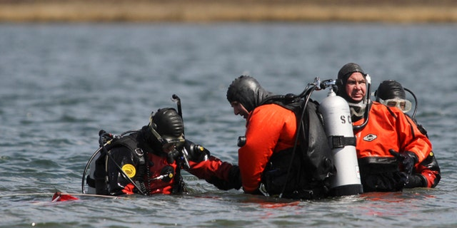 Suffolk County dive team police officers search for possible victims of a suspected serial killer in this April 14, 2011 file photo.