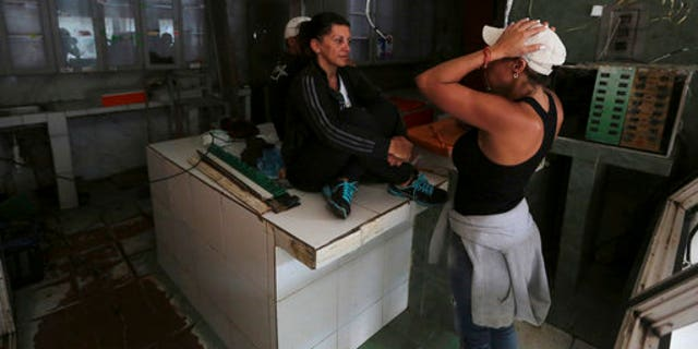 Butcher shop owner Liliana Altuna, left, speaks with an employee inside her shop that was looted the night before, at El Valle neighborhood in Caracas, Venezuela, Friday, April 21, 2017.