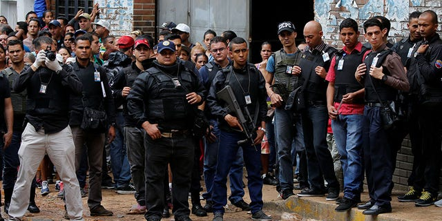 Police officers and criminal investigators look for evidence in front of a bakery after it was looted in Caracas, Venezuela April 21, 2017.