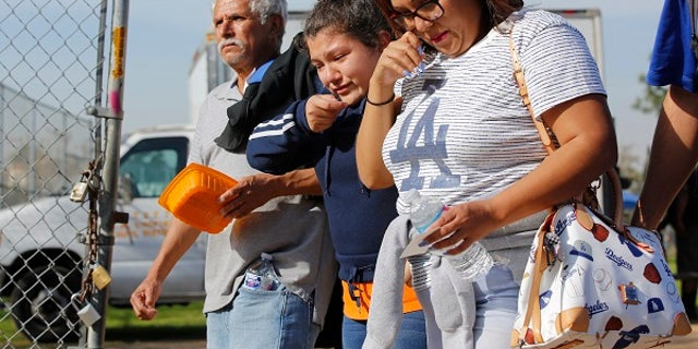 People pick up students following a shooting at the Salvador B. Castro Middle School in Los Angeles.
