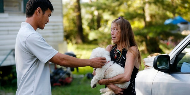 David Phung, who rescued Hailey Brouillette and her dog Sassy from her sinking car in recent floodwaters, reunites with her for the first time in Denham Springs, La., Monday, Sept. 12, 2016.