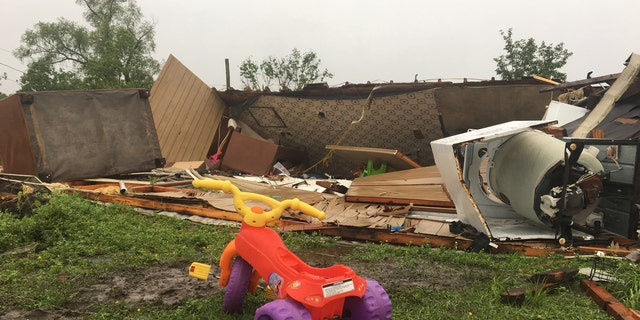 In Breaux Bridge, an EF-1 tornado flipped a trailer upside down, killing a sleeping mother and her 3-year-old daughter. A tricycle with yellow handles and purple wheels sits outside the wreckage Monday morning.