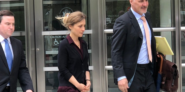 Actress Allison Mack, center, leaves court with her legal team at Brooklyn Federal Court, Friday May 4, 2018, in New York.