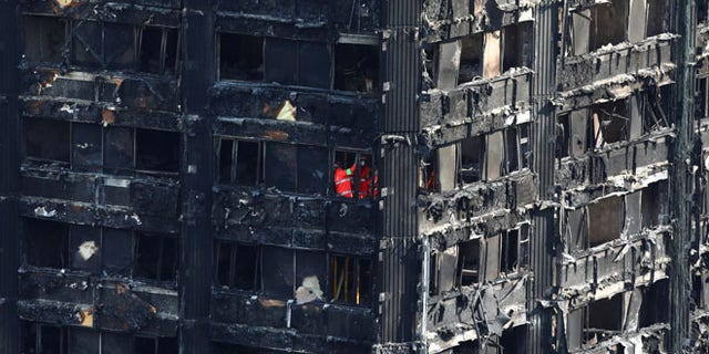Members of the emergency services work inside burnt out remains of the Grenfell apartment tower in North Kensington, London, Britain, June 18, 2017. REUTERS/Neil Hall - RTS17KNS