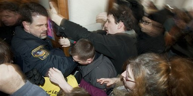 Police try to secure a door during a protest at the Wisconsin state Capitol March 10 in Madison.