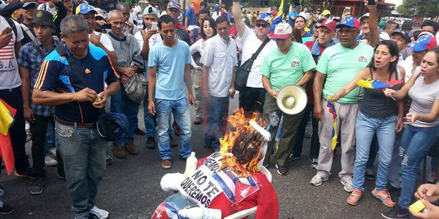 In different points of the city protesters were burning effigies of Maduro, the handpicked successor of late President Hugo Chavez whose socialist rule is blamed for the crippling economic crisis.