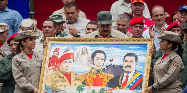 President Maduro holds a painting depicting late President Chavez, Venezuelan liberator Simon Bolivar and himself during march to commemorate 7th anniversary of the Bolivarian Militia in Caracas, Apr. 17, 2017.