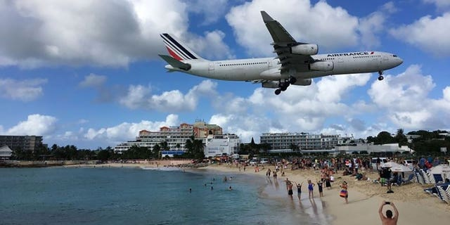 Tourists at Maho Beach in Sint Maarten watch as a plane passes overhead.