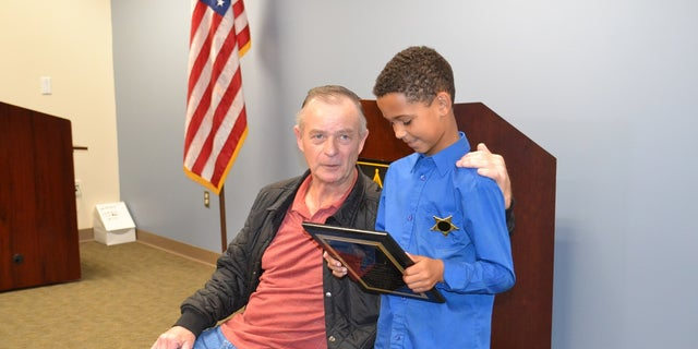 Malachi Coffey inspects his plaque as he stands next to Allen Clemmons. The 65-year-old man was nearly crushed by his Mustang convertible on March 10.