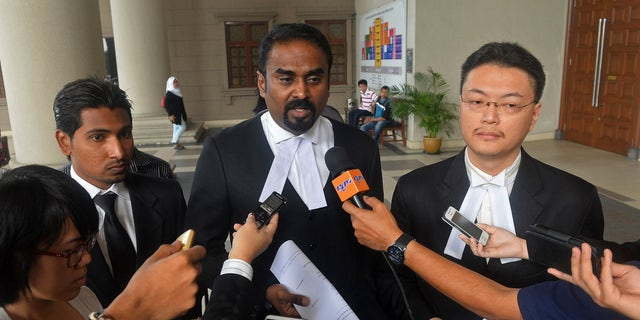 Oct. 31, 2014: Malaysian lawyer Arunan Selvaraj, center, speaks to journalists outside a courthouse in Kuala Lumpur, Malaysia.