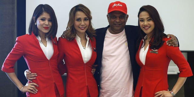 """The uniforms of AirAsia's female flight attendants — a few of whom are seen here posing with AirAsia CEO Tony Fernandes in 2015 — were called """"quite disgusting"""" by the woman in Mamat's letter."""